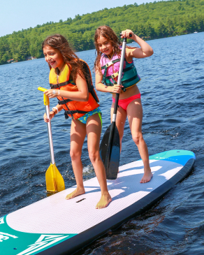 campers stand up paddle boarding