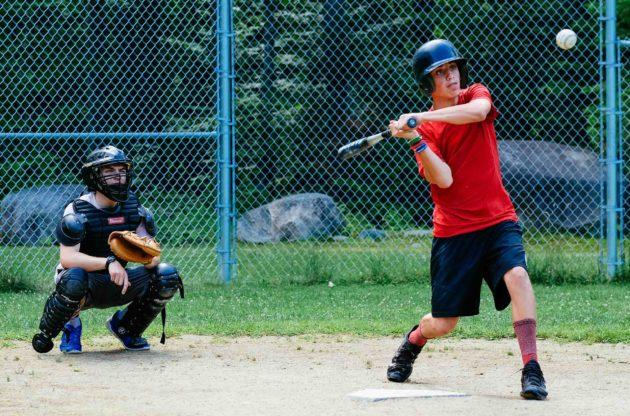 camper hitting a baseball