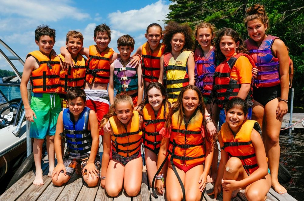 group of campers in life jackets by dock