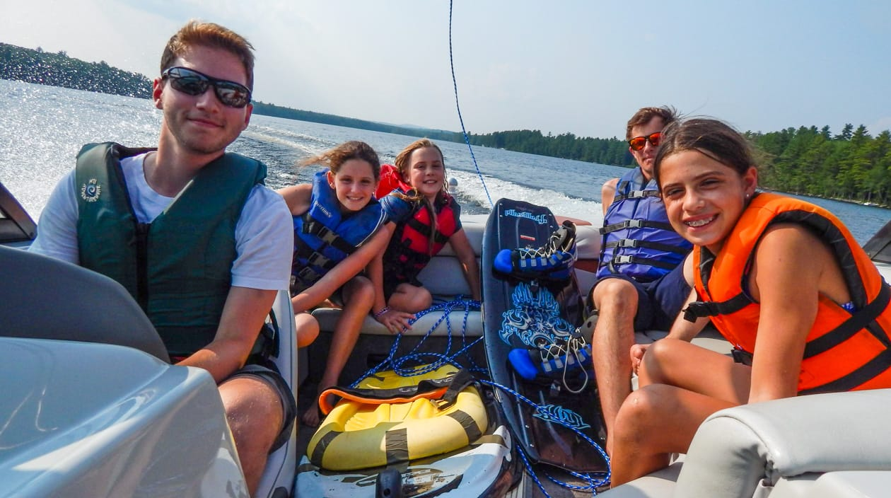 staff and campers on a motorboat