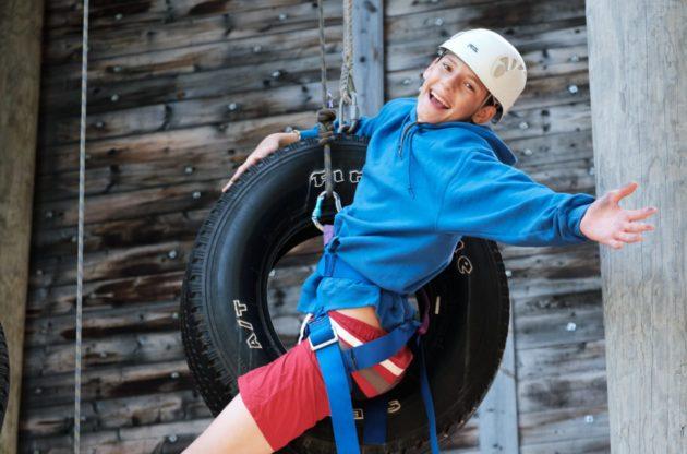 boy hanging onto a tire swing