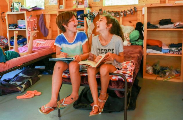 girls laughing while reading on bunk bed