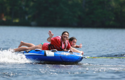Two campers tubing on lake
