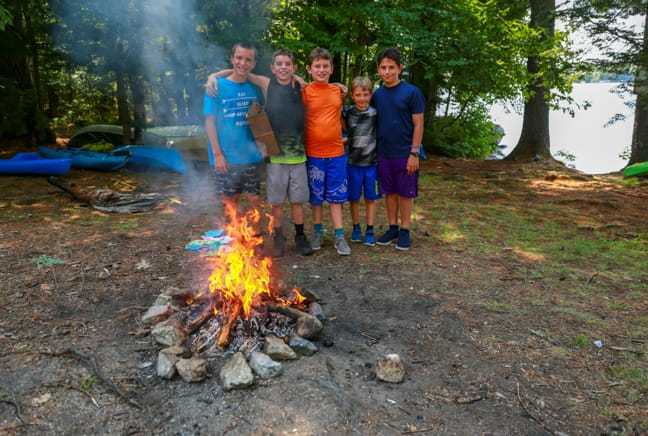 boys by campfire they built for outdoor programming
