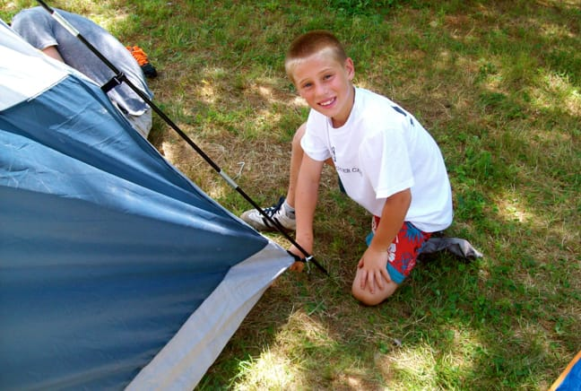 boy setting up a tent