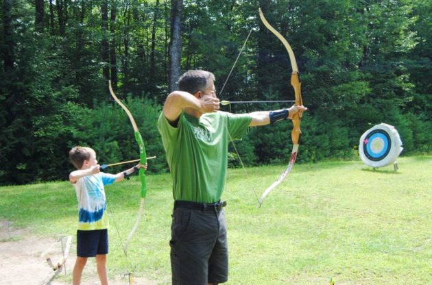 father and son at family camp doing archery