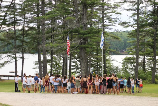 campers by flag pole