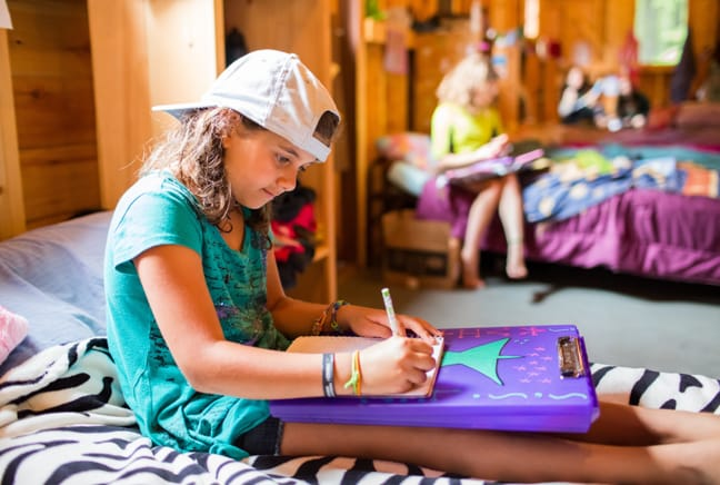 girl writing in the bunk