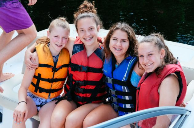 four girls in life jackets on a boat