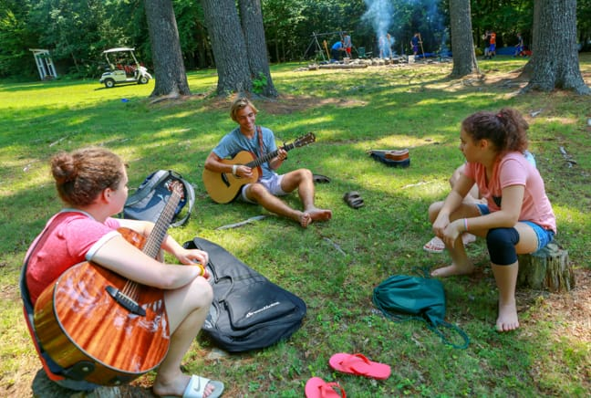 campers outside playing guitar