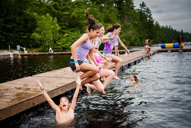 campers jumping off dock into lake