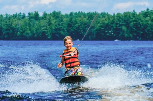 camper kneeboarding on the lake
