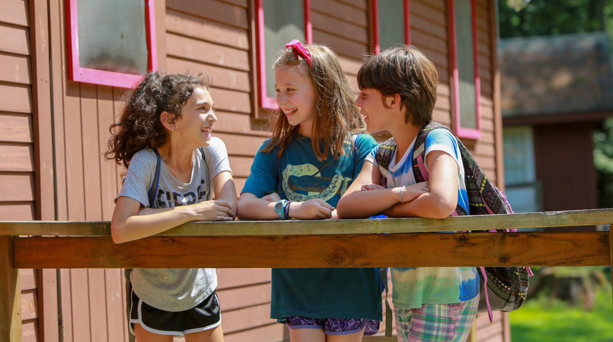 three young campers on cabin porch