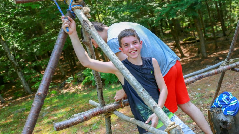 boy by wooden structure he built for outdoor living skills