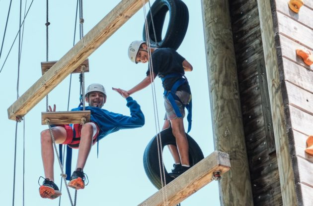 two campers on ropes course high fiving