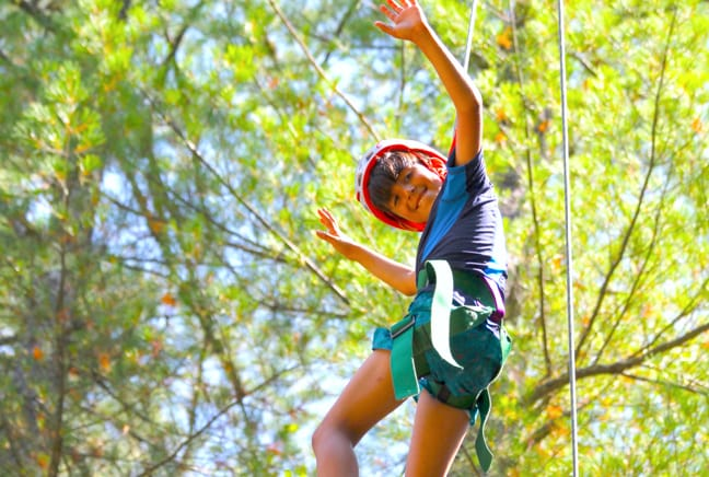 boy crossing ropes course