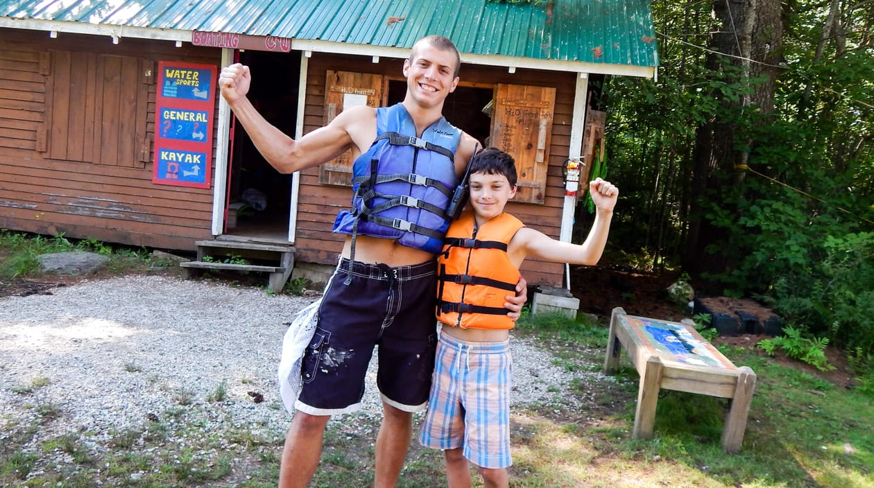 staff and camper wearing life jackets