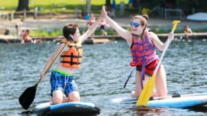 campers high fiving on sup board