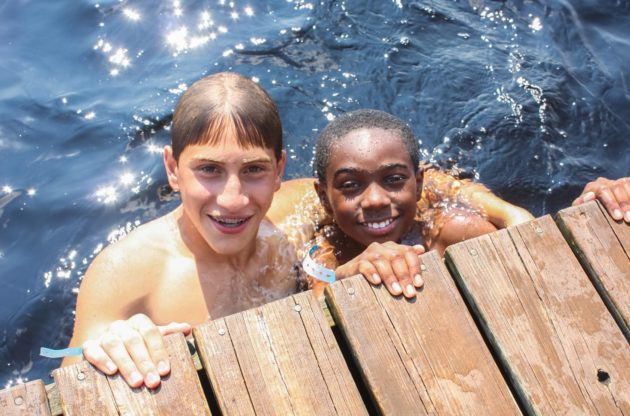 two boys swimming in a lake
