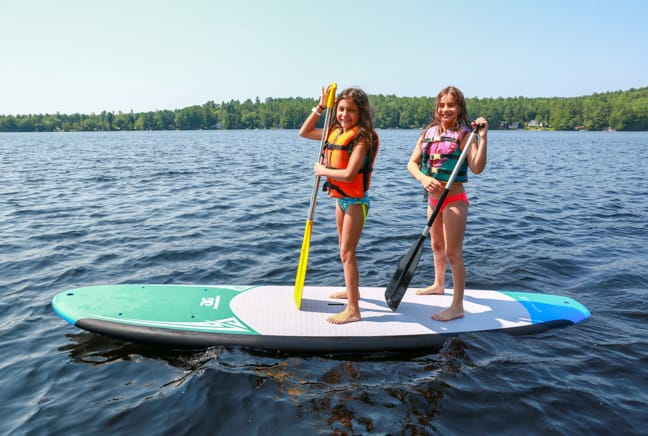 two girls on a stand up paddleboard