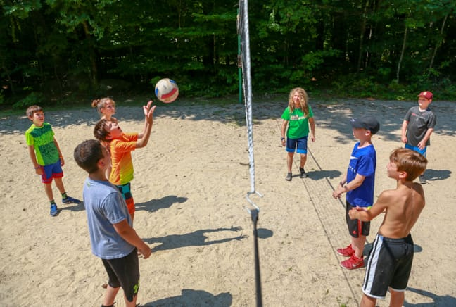 group of campers playing volleyball in the upper fields