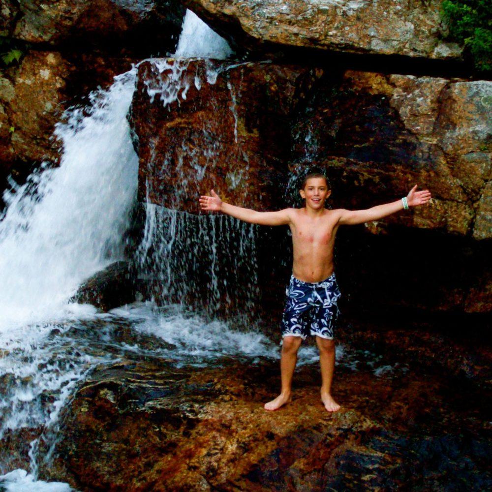boy by waterfall