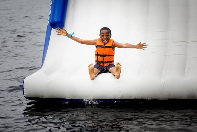 boy sliding off waterslide
