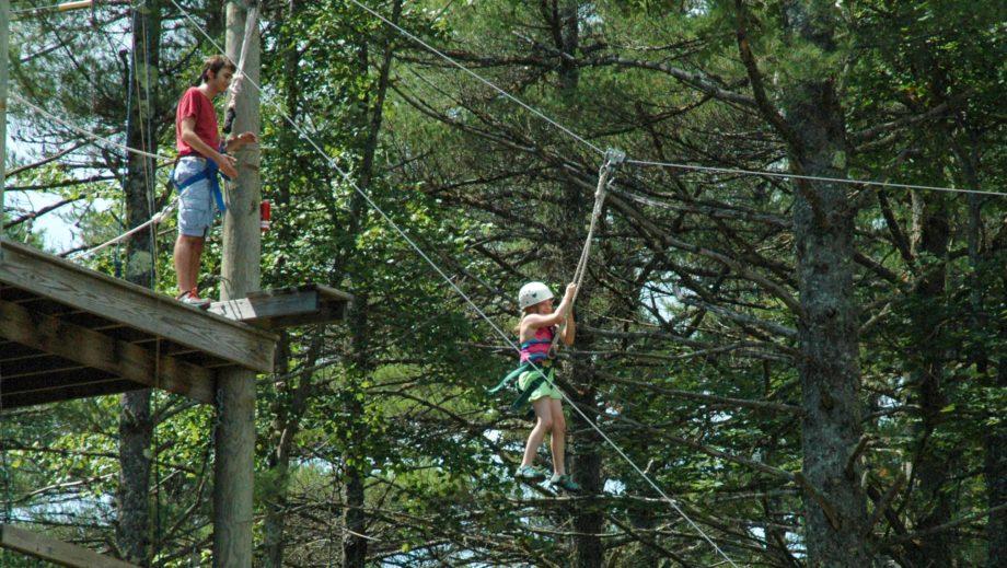 girl ziplining through trees
